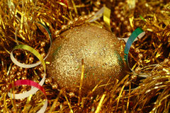 Christmas golden ball. On a golden background Royalty Free Stock Photography