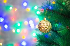 Christmas golden ball on a Christmas tree on a background of sparkles of garlands, bokeh. Royalty Free Stock Image