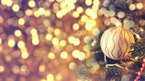 Christmas golden ball hanging on a pine tree. Field to insert text to the left royalty free stock photos