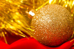 Christmas golden ball and tinsel on red. macro Royalty Free Stock Photos