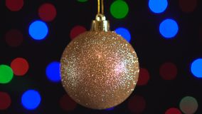 Christmas golden ball toy close-up. Decor with new year tree lights twinkling on background. 4k stock video