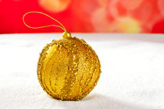 Christmas golden bauble on snow and red Stock Image