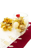 Christmas golden baubles and festive bow. Celebrating Christmas with golden baubles, sparkling heart and festive ribbons. Isolated on white background Stock Images