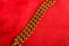 Christmas golden beads on red background Stock Photo