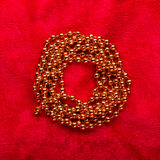 Christmas golden beads on red background Stock Photography