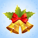 Christmas golden bells with holly leaves and festive red bow. On snowflakes background Stock Photos
