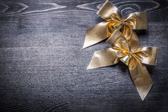 Christmas golden bows with bells on wooden board Royalty Free Stock Photo