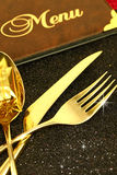 Christmas golden cutlery and restaurant menu. On festive background Stock Photo