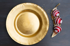 Christmas golden plate. Christmas empty golden plate with red decorations Stock Photo