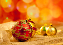 Christmas golden and red baubles in blur lights. Background Royalty Free Stock Photo