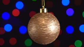 Christmas golden shiny ball toy is spinning close-up. Decor with new year tree lights twinkling. On background. 4k stock video footage
