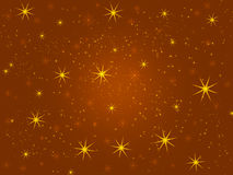 Christmas golden shiny yellow stars on the brown background, light effect Stock Images