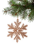 Christmas golden snowflake. Hanging on a spruce on white background stock images