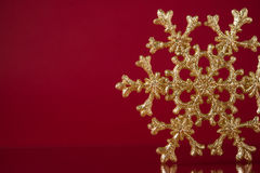 Christmas golden snowflake on dark red background with space for text. Xmas holiday theme Royalty Free Stock Photo