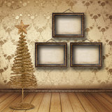 Christmas golden spruce in the old room. Decorated with wallpaper Stock Image