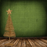Christmas golden spruce in the old room. Decorated with wallpaper Stock Photo