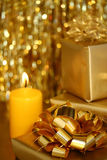 Christmas - Golden Theme III. Three golden Christmas boxes, golden ribbon in the front, blurred yellow candle and glittering strings in the background Stock Images