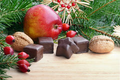 Christmas goodies with Christmas decoration. Christmas goodies in Christmas decoration, red apple, chocolate, walnut, fir branches and rose hips, copy space royalty free stock photo