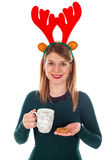 Christmas goodies. Picture of a smiling young woman with raindeer slide holding a cup of tea and a cookie Stock Photography