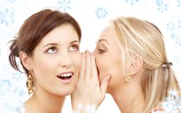 Christmas gossip. Two happy young girlfriends with twinkles and snowflakes royalty free stock images