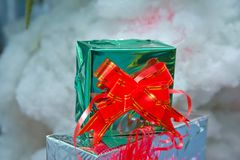 Green gift box with out of focus lights on a snow background . Christmas green boxes with snow , christmas images, in blurred. Christmas green boxes with snow stock image