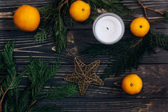 Christmas green branches and oranges and golden star on black ru. Stic wooden background. seasonal greeting card and advertising concept. space for text. flat stock images
