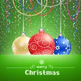 Christmas green card with snow around and baubles Royalty Free Stock Photography