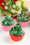 Christmas green cupcakes with festive decorations stock images