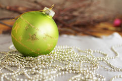 Christmas green glass sphere on a fir-tree. Christmas green glass sphere with gold stars on brilliant garlands for decoration of a fir-tree Stock Photography