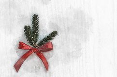 Christmas green spruce branch with a red ribbon on a wooden background royalty free stock image