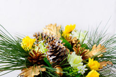 Christmas greenery with golden cones and yellow silk roses Stock Images