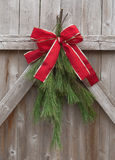 Christmas Greens. Tied with red ribbon on a rustic wood fence Stock Photo