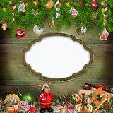 Christmas greeting background with frame, Christmas toys, pine branches, sweets. Green wooden background with pine branches, Christmas decorations Royalty Free Stock Photos