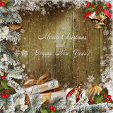 Christmas greeting background with gifts, pine branches and Christmas decorations. Gifts, Christmas decorations, pine branches and berries on a wooden snowy Stock Image