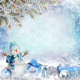 Christmas greeting background with pine branches, snowman and gifts. Winter blue background with pine branches, snowman, gifts, balls Royalty Free Stock Images