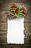 Christmas greeting card. On wooden top, with holly and pine cone stock photos