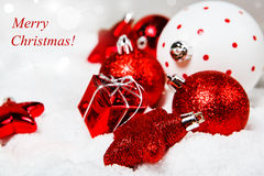 Christmas greeting card. With red decoration in snow Royalty Free Stock Images