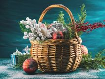 Christmas greeting card with basket and decoration. Christmas greeting card with basket full of holiday decorations. Festive new year background with gifts and Royalty Free Stock Images
