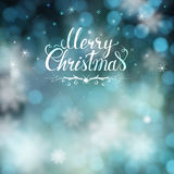 Christmas greeting card with blur background and hand-drawn lettering Stock Photography