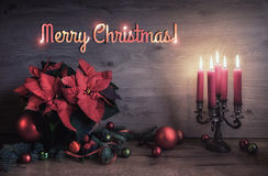 Christmas greeting card with candles and decorations on wooden Stock Image