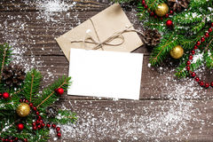 Christmas greeting card with envelope on wooden background. With fir tree branches and happy new year decorations covered with snow Royalty Free Stock Photography