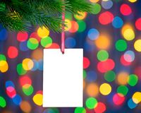 Christmas Greeting Card on the Fir Branch on the Holiday Lights Background Royalty Free Stock Photos