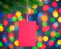 Christmas Greeting Card on the Fir Branch on the Holiday Lights Background Stock Images