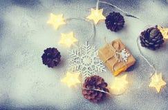 Christmas greeting card with gift box, pine cones, star light ga Stock Photography