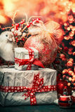 Christmas greeting card with gift boxes,red decoration ball and bird at festive bokeh lighting background, vertical Stock Images