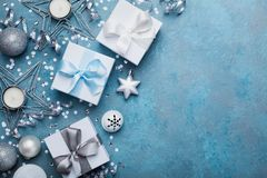 Christmas greeting card. Gift boxes, silver balls, confetti, star and sequins on blue vintage table top view. Flat lay. Royalty Free Stock Photography