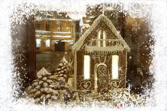 Christmas greeting card with gingerbread house and snowman in frame of white snowflakes on background of night city stock photos