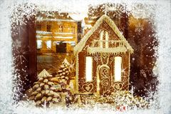 Christmas greeting card with gingerbread house and snowman in frame of white snowflakes on background of night city royalty free stock images