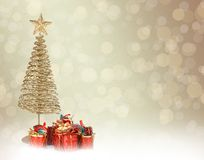 Christmas greeting card with gold metal firtree. And presents on the abstract background Stock Image