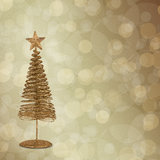 Christmas greeting card with gold metal firtree. On the abstract background with bokeh effect Royalty Free Stock Image